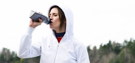 Kvinne som drikker etter trening