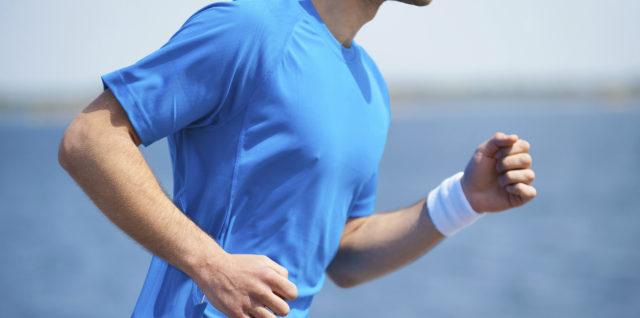 Enjoying a morning run.  Side view of young man running along the riverbank