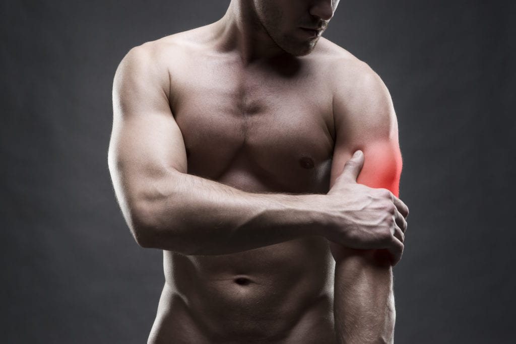 Pain in the elbow. Muscular male body. Handsome bodybuilder posing on gray background